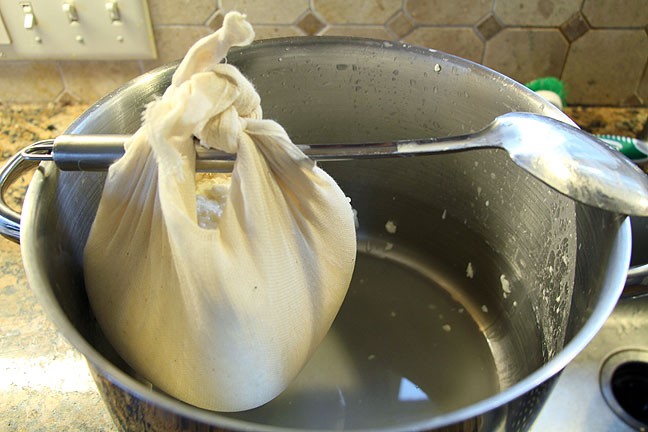Hang homemade feta in cheesecloth to drain