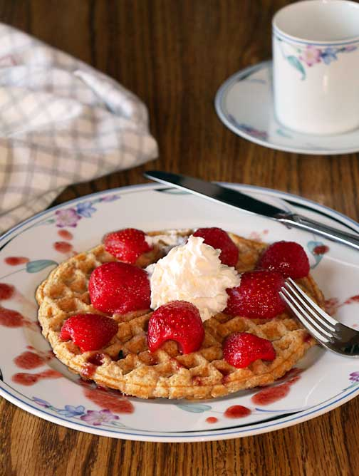 Eating whole wheat waffles and berries for breakfast