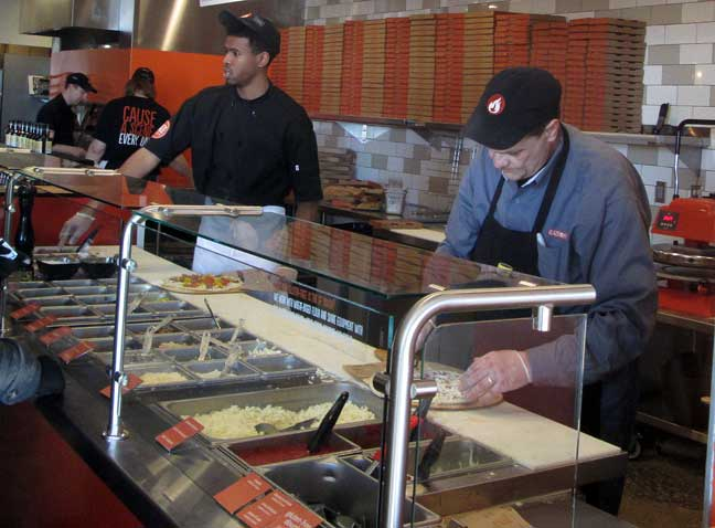 Assembling the pizza at Blaze Pizza