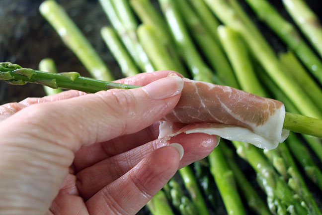 wrapping asparagus spear with prosciutto