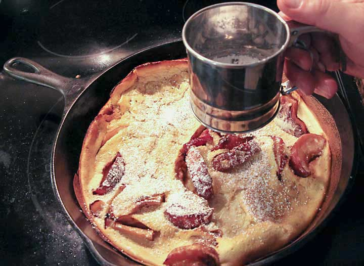 Sprinkle Apple Dutch Baby Pancake with powdered sugar