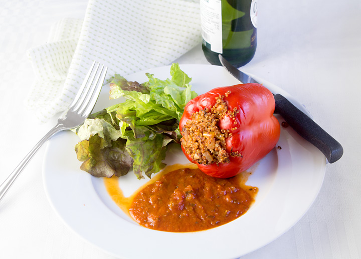 Quinoa Stuffed Peppers combine healthy red peppers with nutritious quinoa, savory tomato sauce and herbs for a tasty vegan entree. You won't miss the meat!