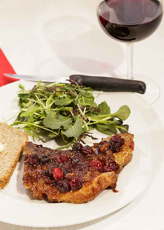 """Cranberry Glazed Pork Chops are elegant and """"comfy"""" at the same time. The savory pork and glistening berries make it a perfect dish for Valentine's Day or Christmas dinner."""