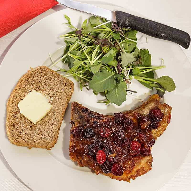 """Cranberry Glazed Pork Chops are elegant and """"comfy"""" at the same time. The savory pork and glistening berries make it a perfect dish for Valentine's Day or Christmas dinner.;"""