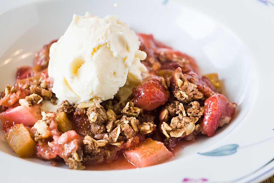 Sweet strawberries and tart rhubarb combine perfectly in this Maple Strawberry Rhubarb Crisp -- sweetened by maple syrup (no sugar!) and sprinkled with a crunchy oatmeal topping!