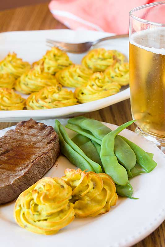 An elegant dish of mashed and flavored potatoes piped into rosettes, pommes duchesse can turn the humble potato into a beautiful and impressive side.