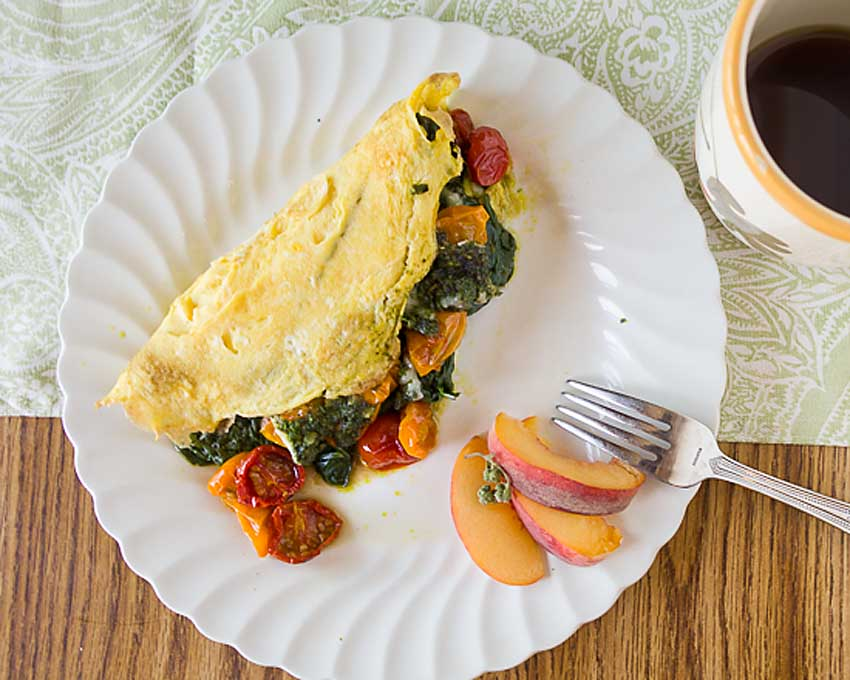 Bursting with flavor, this Roasted Tomato Omelet with Spinach, Pesto & Cheese pairs savory pesto with sweet smoky roasted tomatoes for a perfect fall combo.