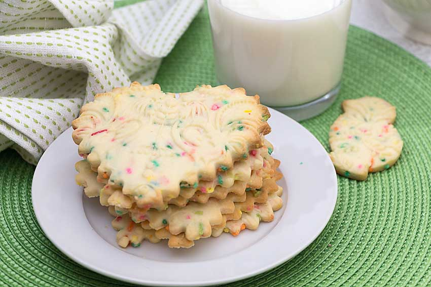 Use the right recipe. To retain your design, you will need to use a recipe that is less moist and lower in leavening-- baking soda and extra butter are not your friends here. Light, puffy cookies won't keep the sharper edges you want here.