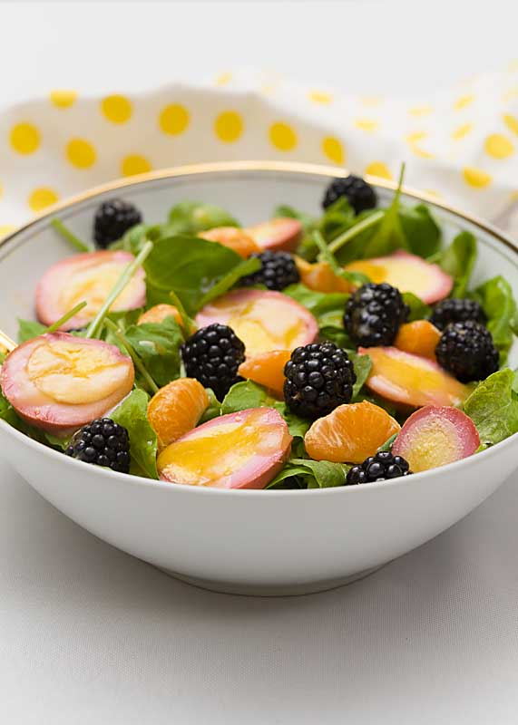 Dressed up in fun spring colors this colorful Easter Salad pulls together purple blackberries, green arugula, oranges and pink pickled eggs.