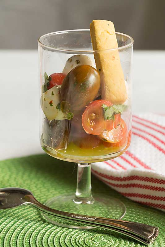 Cherry Tomatoes, Fresh Mozzarella balls and basil in a wine glass, Deconstructed Caprese Salad Appetizer is perfect for a dinner party or nice picnic.