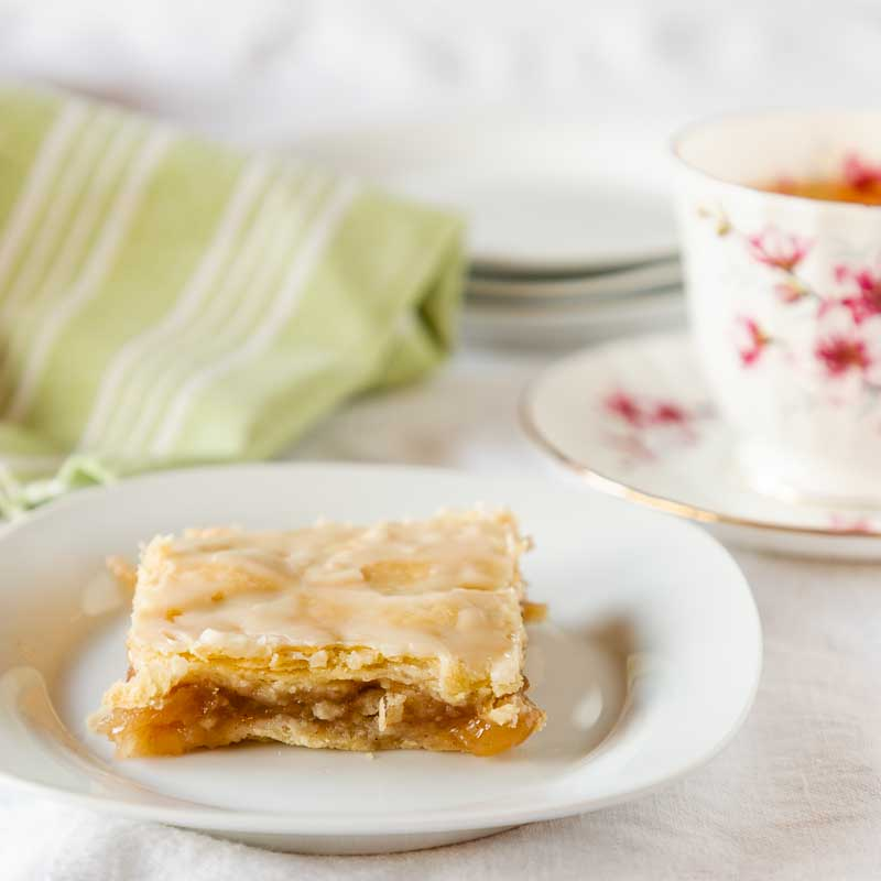 Glazed Apple Pie Bars are like a special slab pie--rich pie crust topped with apples, more crust, then glaze. Cut into bars, they are easy and delicious!