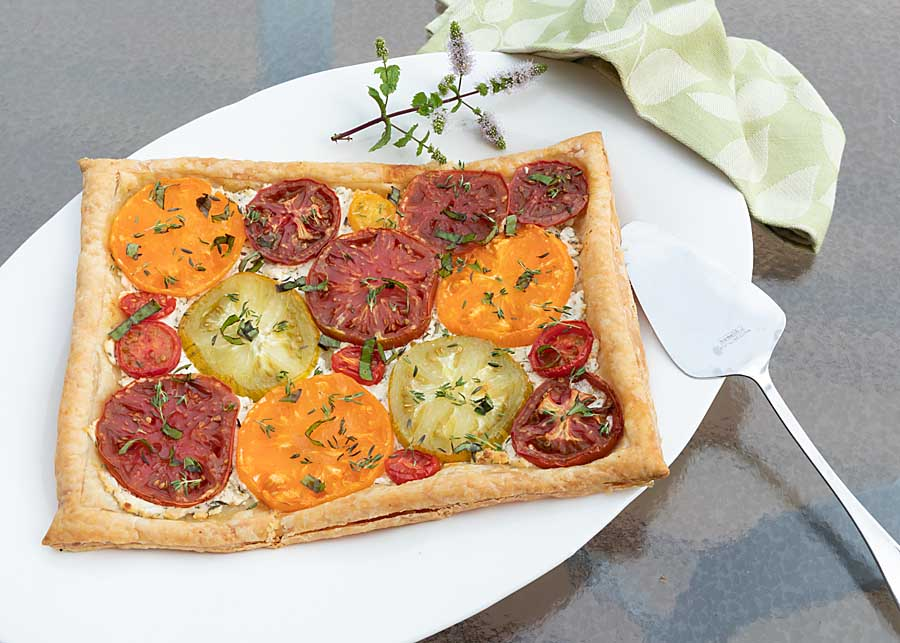 Crisp puff pastry, savory herbed cheese, luscious ripe tomatoes & chopped fresh herbs make this Heirloom Tomato Tart a perfect side dish or appetizer.