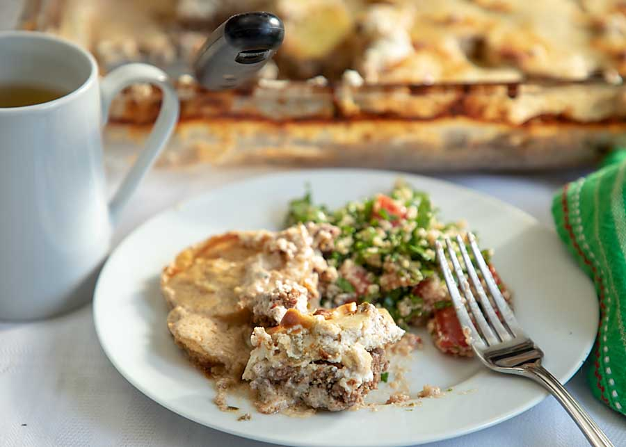 Kufta in Tahini Sauce (or kofta or kefta) is ground meat mixed with parsley, onions, garlic and spices! Topped with potatoes and Tahini Sauce it's a Middle Eastern delight.