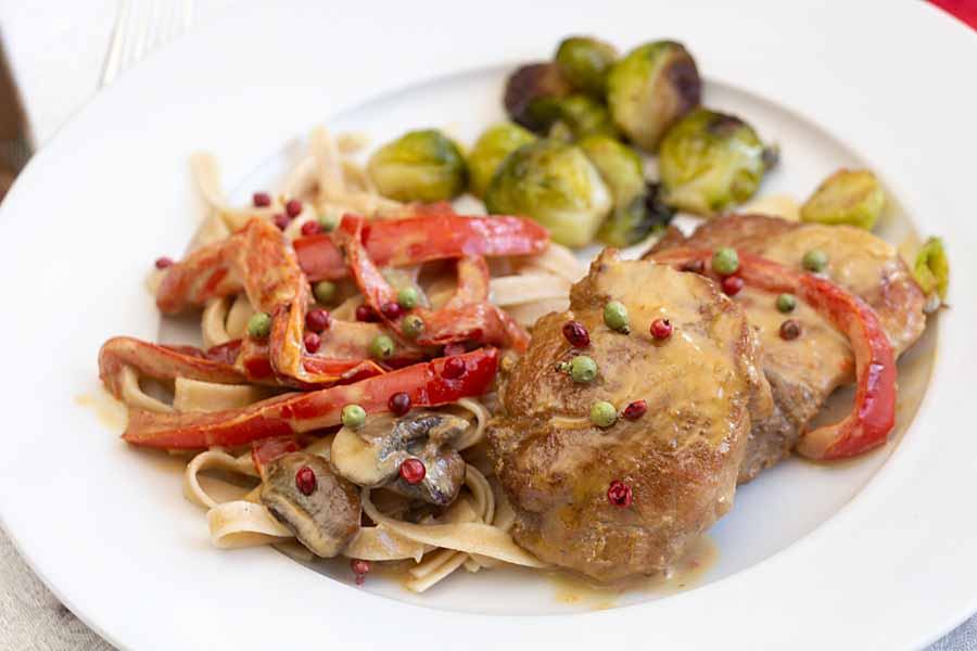 Pork in Brandy Cream Sauce pairs tender meat with ripe peppers, mushrooms, brandy and cream then garnishes it all with pink and green peppercorns.