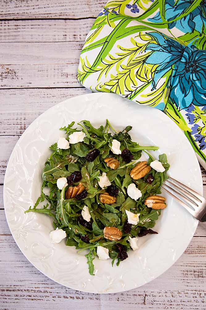 With a creamy vinaigrette dressing, this Sweetened Goat Cheese Arugula Salad adds cranberries and pecans for maximum flavor.