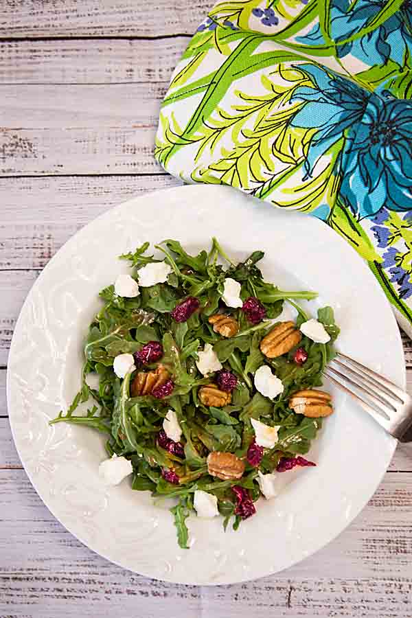 With a creamy vinaigrette dressing, this Sweetened Goat Cheese Arugula Salad adds dried cranberries and pecans for maximum flavor.
